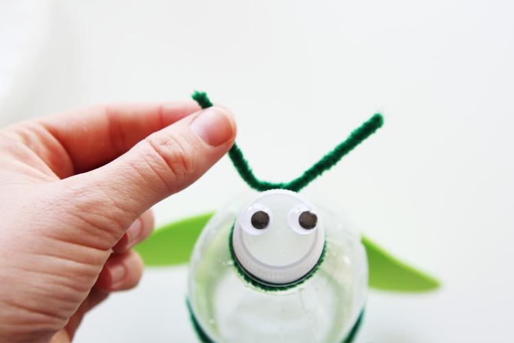 چسباندن چشم پلاستیکی روی سر بطری نوشابه در کاردستی زنبورک شب تاب